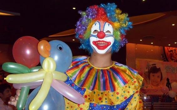 """一提及小丑,很多人最先想到的就是脸上五彩斑斓、鼻尖顶着小红球、穿着奇怪衣服的滑稽形象。10多年前,职业小丑在国内并不多见。如今,在一些大城市,婚礼、开业典礼现场或是生日派对上,职业小丑表演已经不稀奇了。   时松明就是一名职业小丑,今年42岁的他,进入小丑表演这一行已经10年了。   """"这是表面看上去轻松喜剧,事实上却非常辛苦的一份工作。""""时松明说。   从2010年来到台州从事专职小丑表演至今,时松明感受到了这一行业在台州从无到有,逐渐兴起的态势。   """"人数增加"""